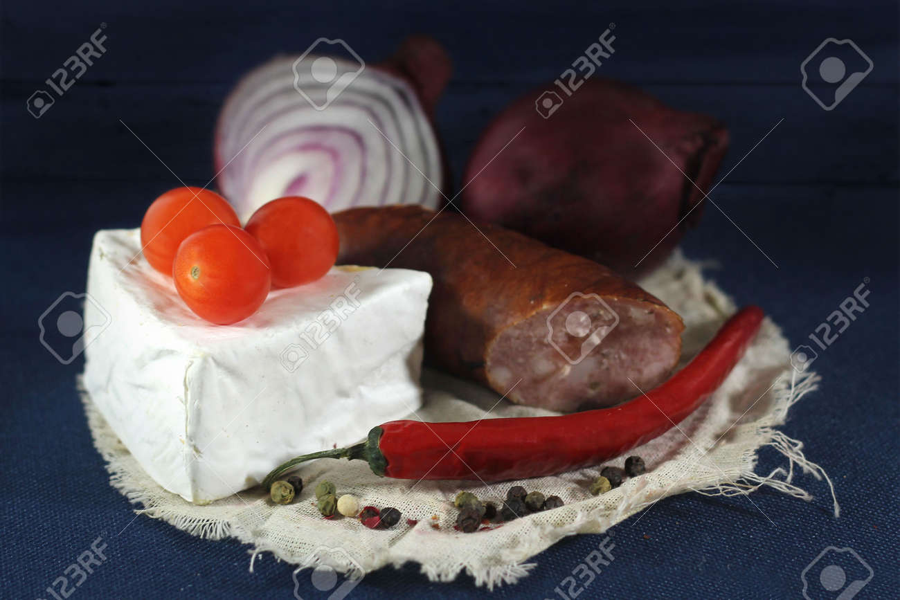 Arrangement with sausage , tomatoes and white cheese on  blue background Stock Photo - 17567765