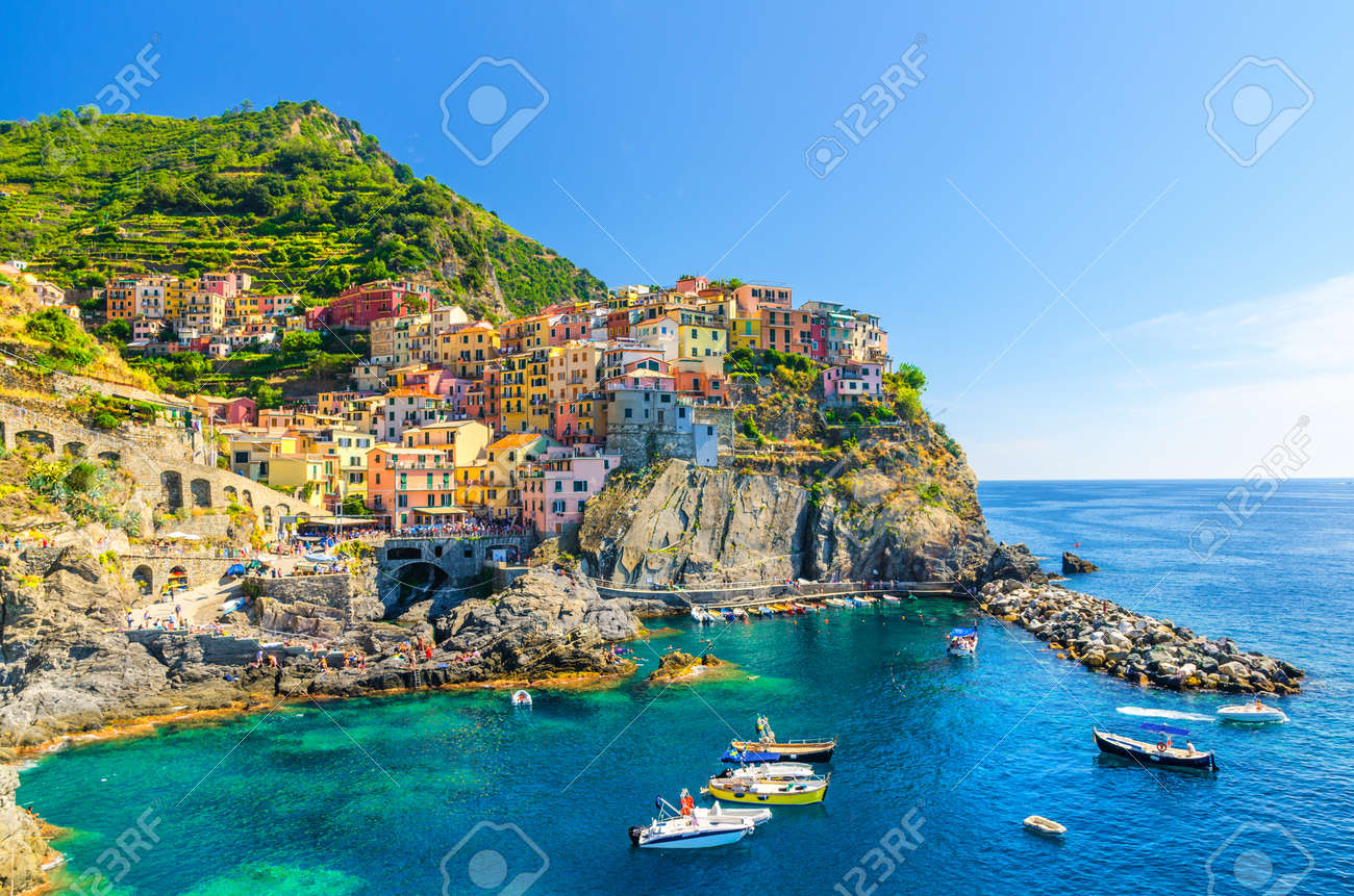 Manarola traditional typical Italian village in National park Cinque Terre, colorful multicolored buildings houses on rock cliff, fishing boats on water, blue sky background, La Spezia, Liguria, Italy - 123537178