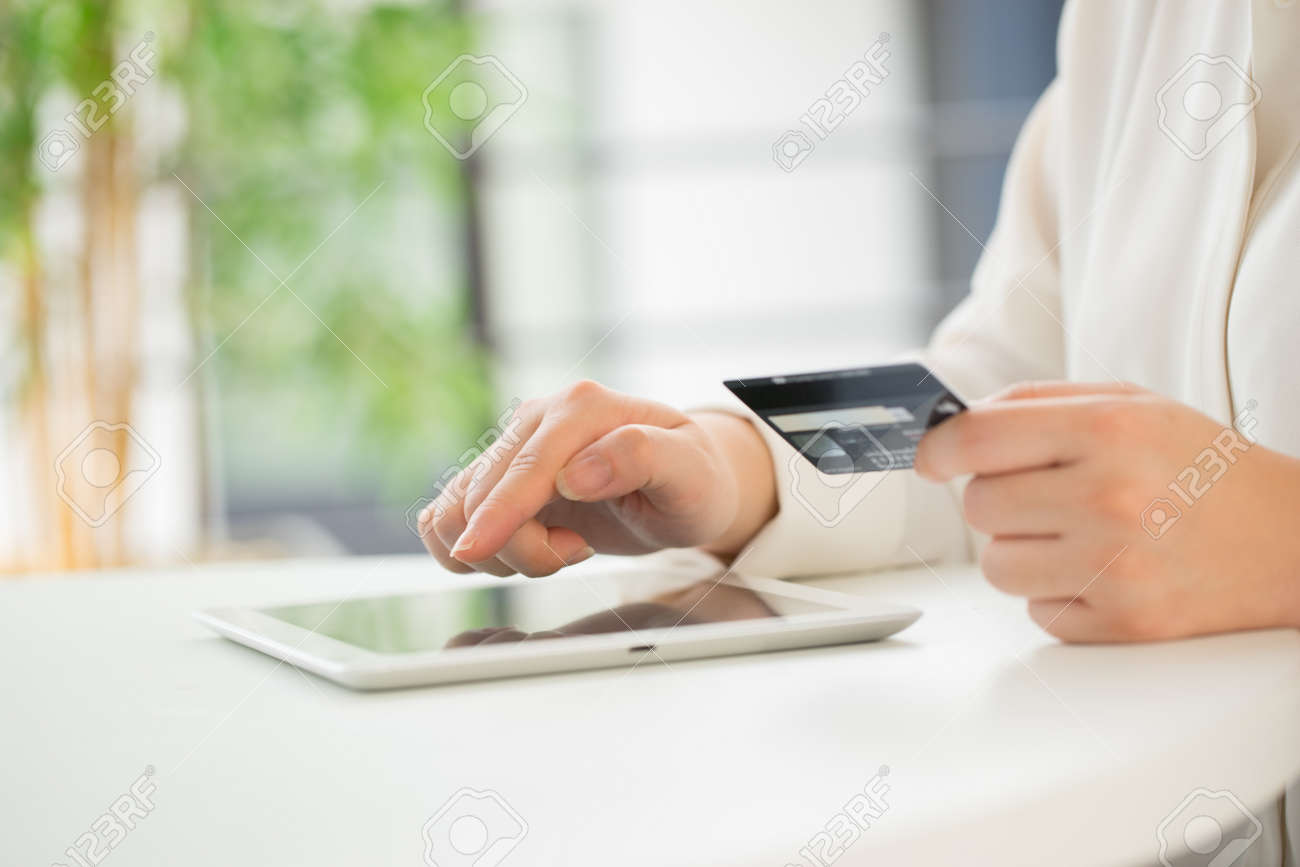 Hands of an office woman typing keyboard with credit card - 43143853