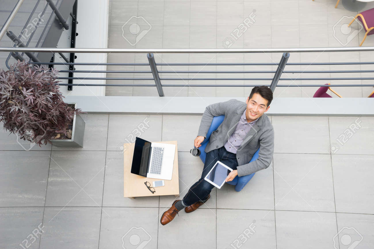 Young asian businessman using tablet, mobile phone in the office - 44147237