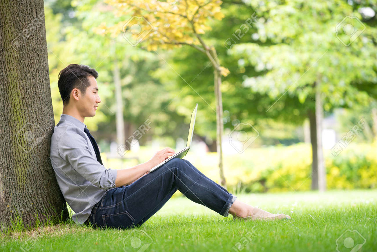 Young asian & success businessman using tablet, laptop, mobile phone in the park - 44147925