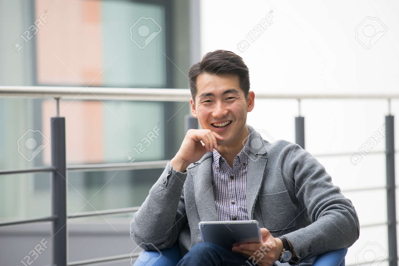Young asian businessman using tablet, mobile phone in the office - 44437963
