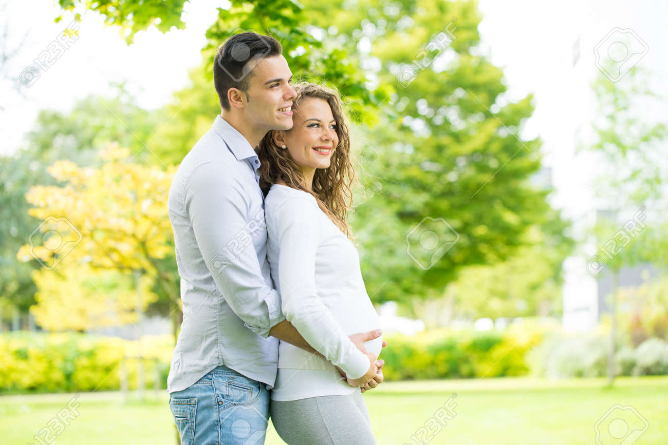 Happy and young pregnant couple in park in summer - 45030111