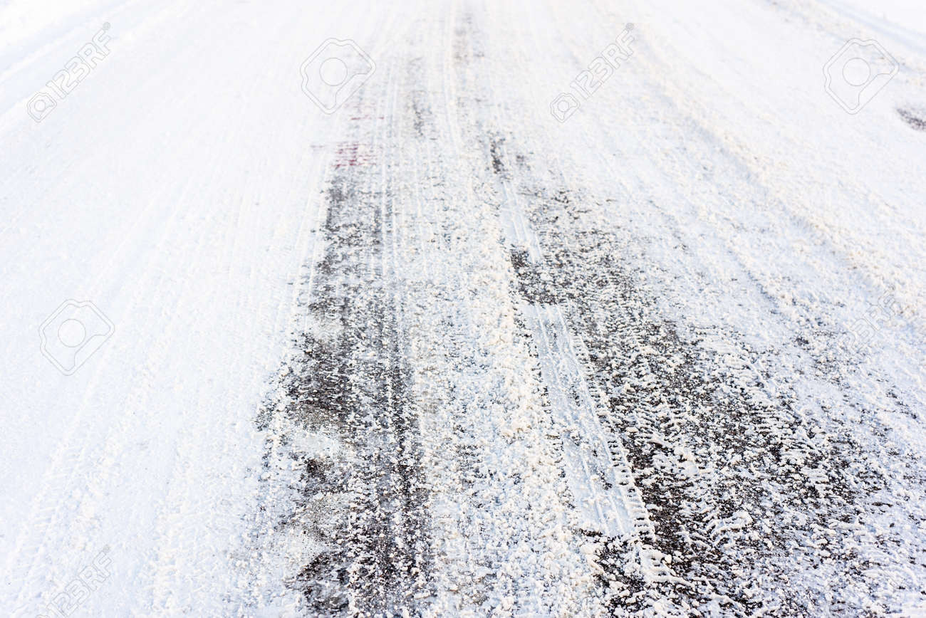 country road in winter asphalt covered snow with tire tracks