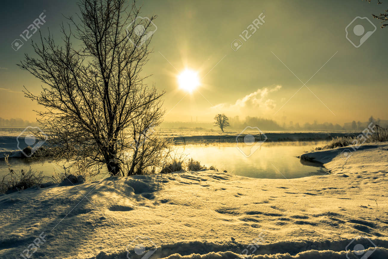 winter river landscape, moody scenery with morning sun reflection