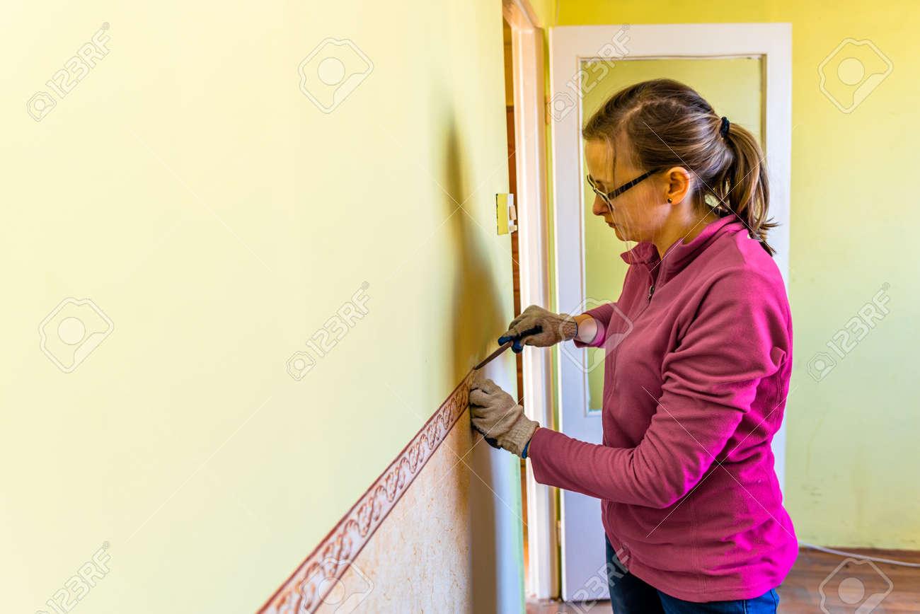 壁から古い壁紙を削除する女性 家のリノベーションの概念 の写真素材 画像素材 Image