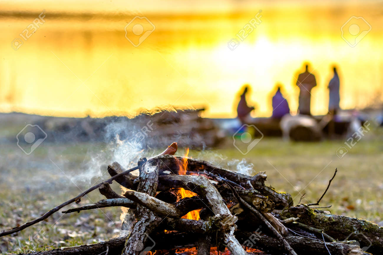 Group of friends on camp with campfire and sausages grilling over fire and smoke - 102045851
