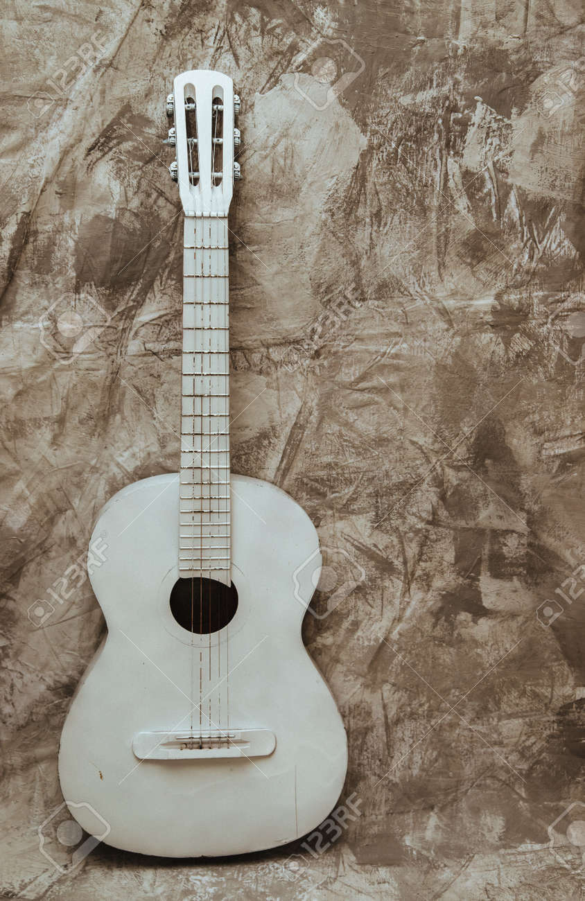 A white old guitar stands against a textured gray wall. Guitar as an object in the interior. Decor and decoration. Broken guitar. - 161360156