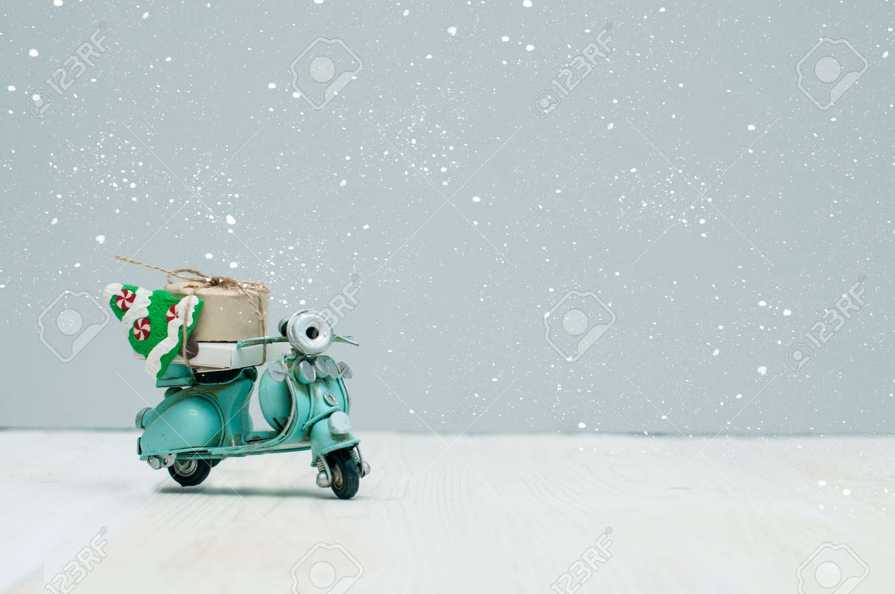 Stock Photo - Vintage toy motorbike with christmas gifts and tree on grey background
