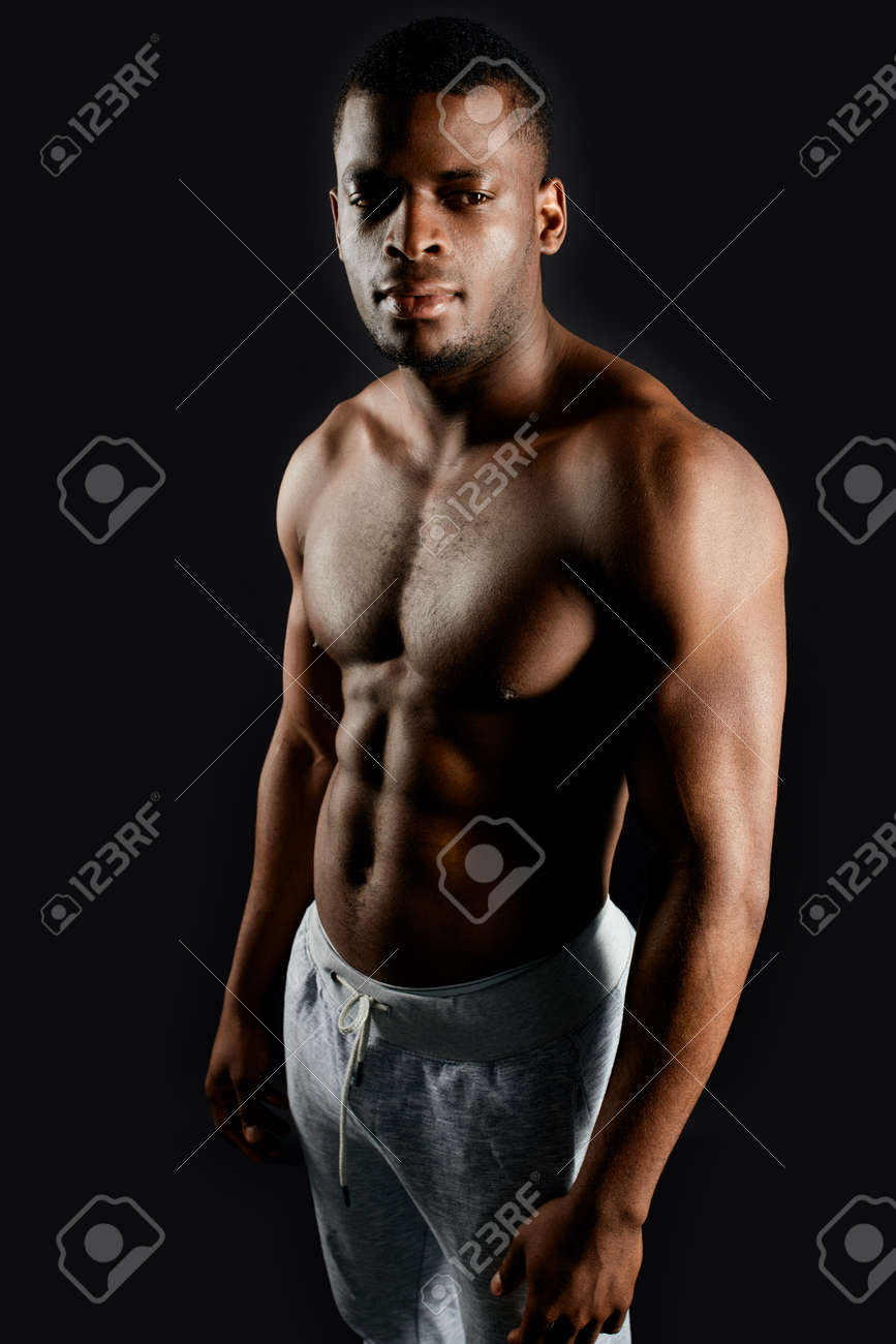 pleasant handsome african guy with beautiful body standing over black background.appearance, people concept - 128317879