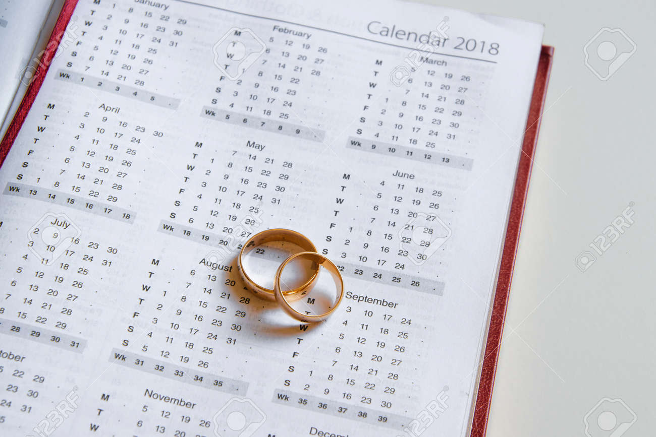 planning a wedding in 2018 calendar of 2018 and two wedding rings on white background