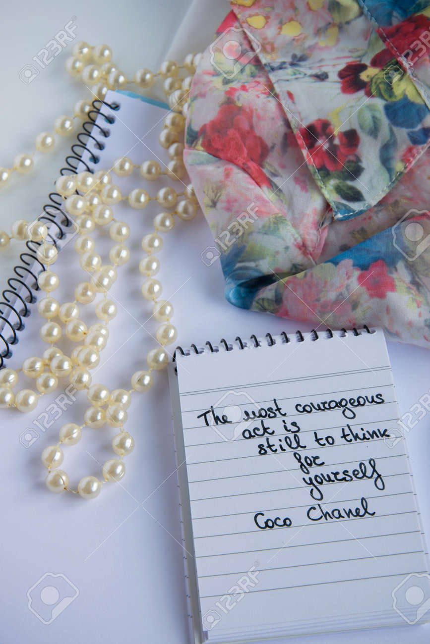 Coco Chanel quotes written on a block note, pearl accessories..