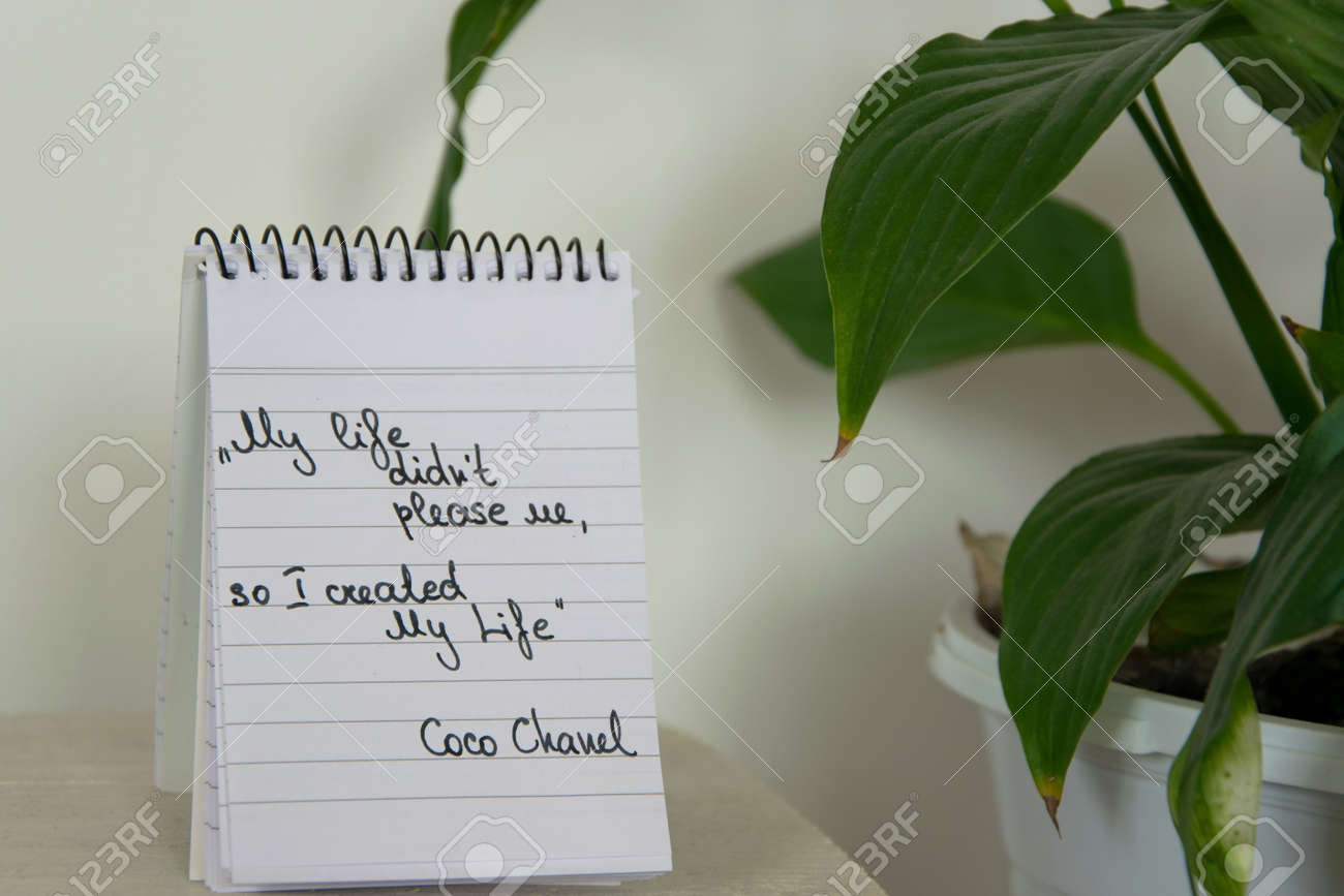 Coco Chanel quotes written on a block note and potted houseplant,..