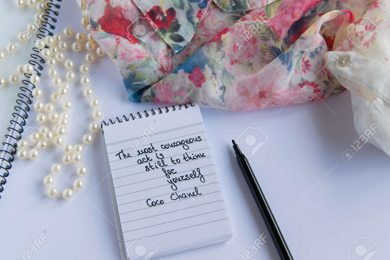 0a3b18ba7 Coco Chanel quotes written on a block note, pearl accessories and and silky flower  shirt