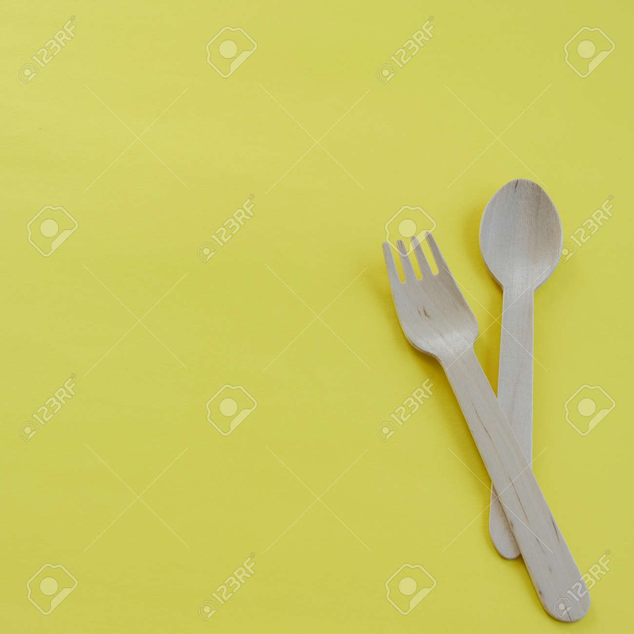 Bamboo wooden spoons and forks on yellow background with space..