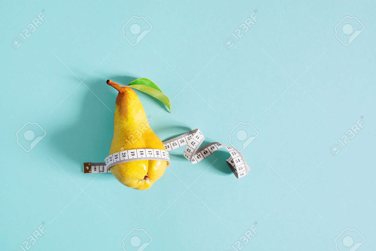 Weight loss concept, yellow pear checks body shapes with measuring tape, blue background - 168917300