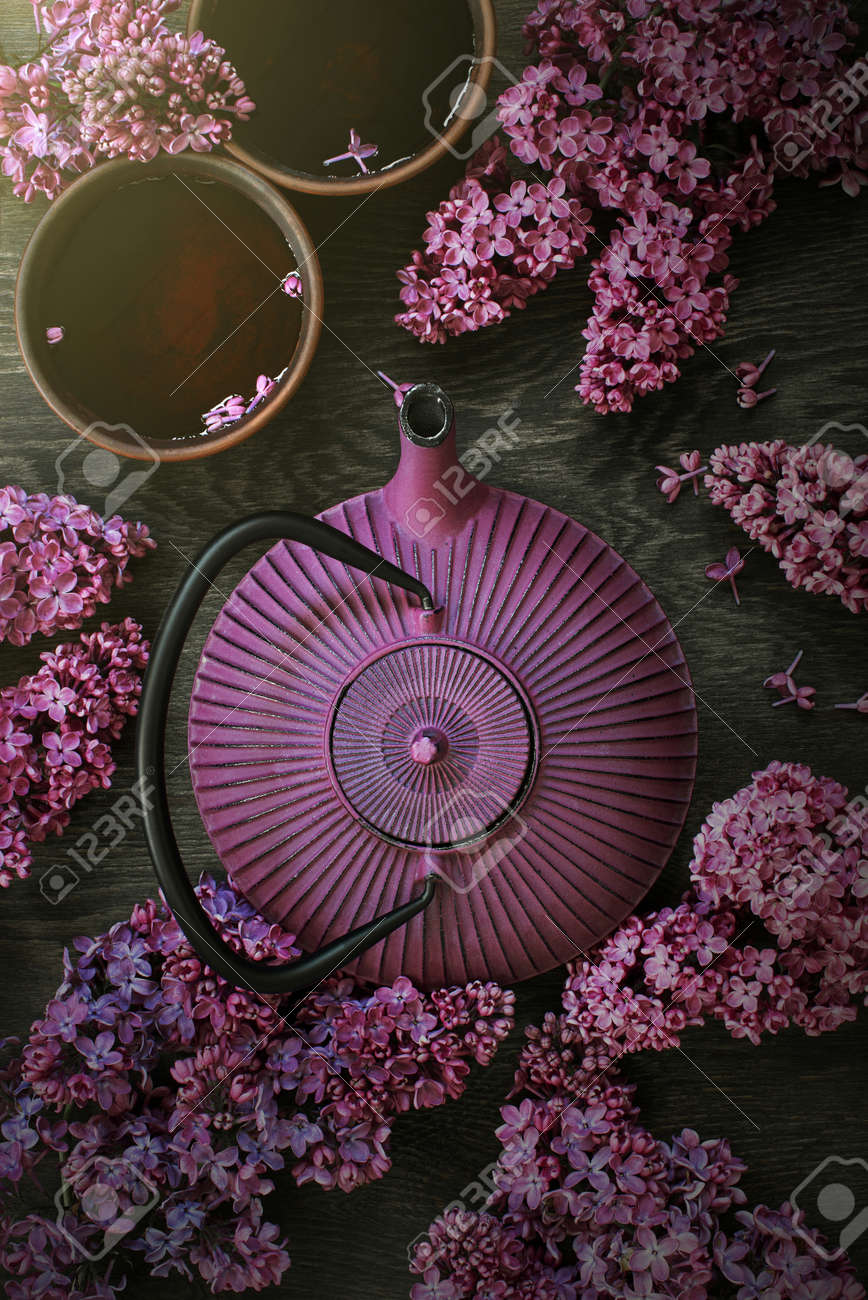 Teapot and two cups of tea on the dark wooden table decorated with blooming lilac, top view - 168917302