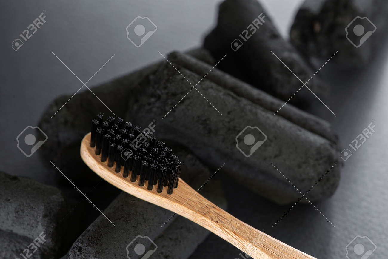 Bamboo toothbrush with charcoal bristles on the charcoal pieces, closeup - 168917551