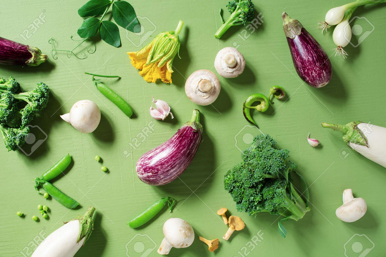 Fresh raw organic vegetables on the textured green table, concept of healthy eating and organic gardening, top view - 168917552