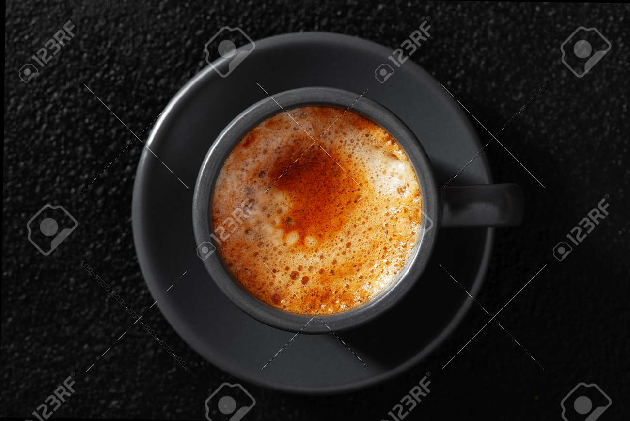 The cup of espresso coffee on black table, closeup overhead view - 168918084