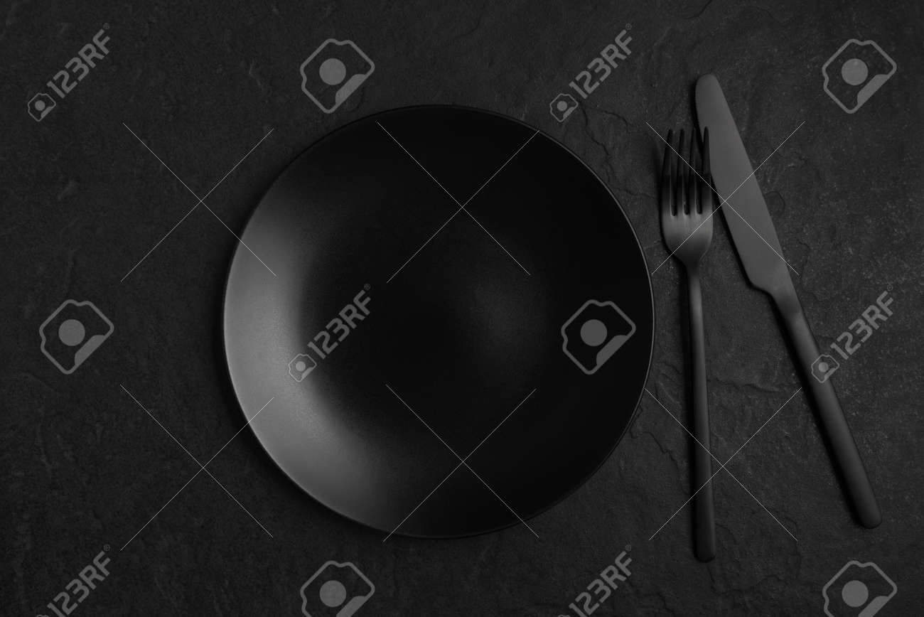 Black background with plate and cutlery, monochrome table setting - 168918083