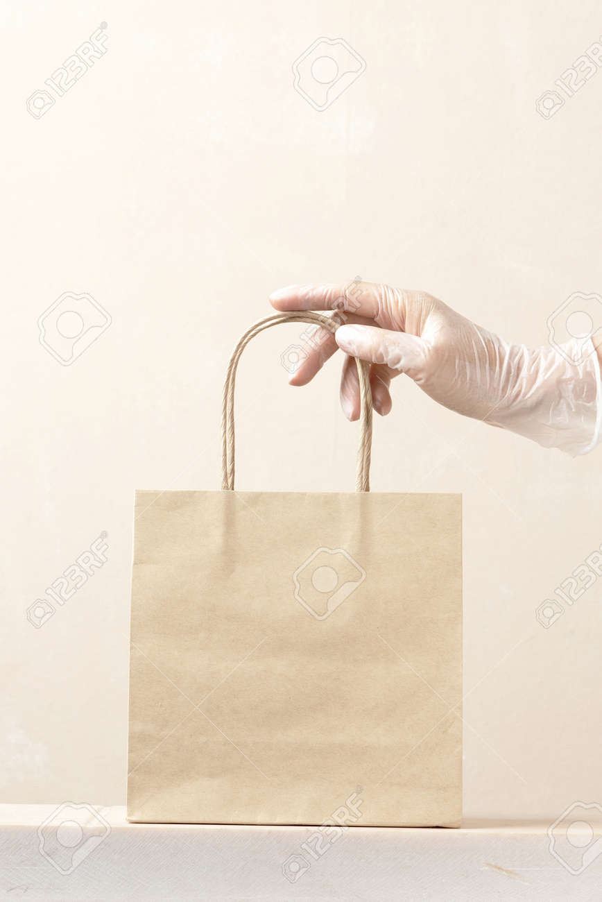 Concept of safe delivery in the period of pandemic. Gloved hand holding the paper bag. - 168918092