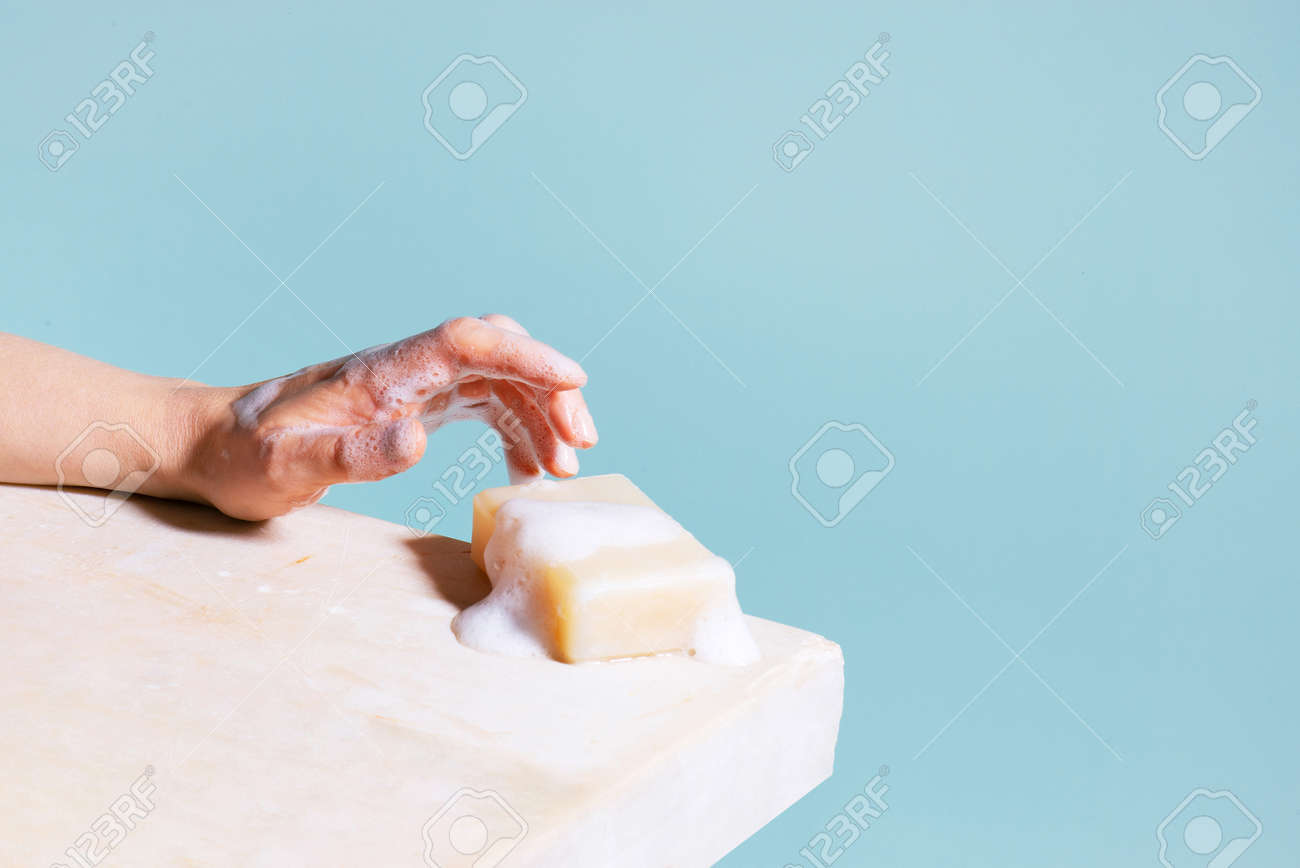 Piece of white soap and female hand with foam, concept of antibacterial protection - 168918305