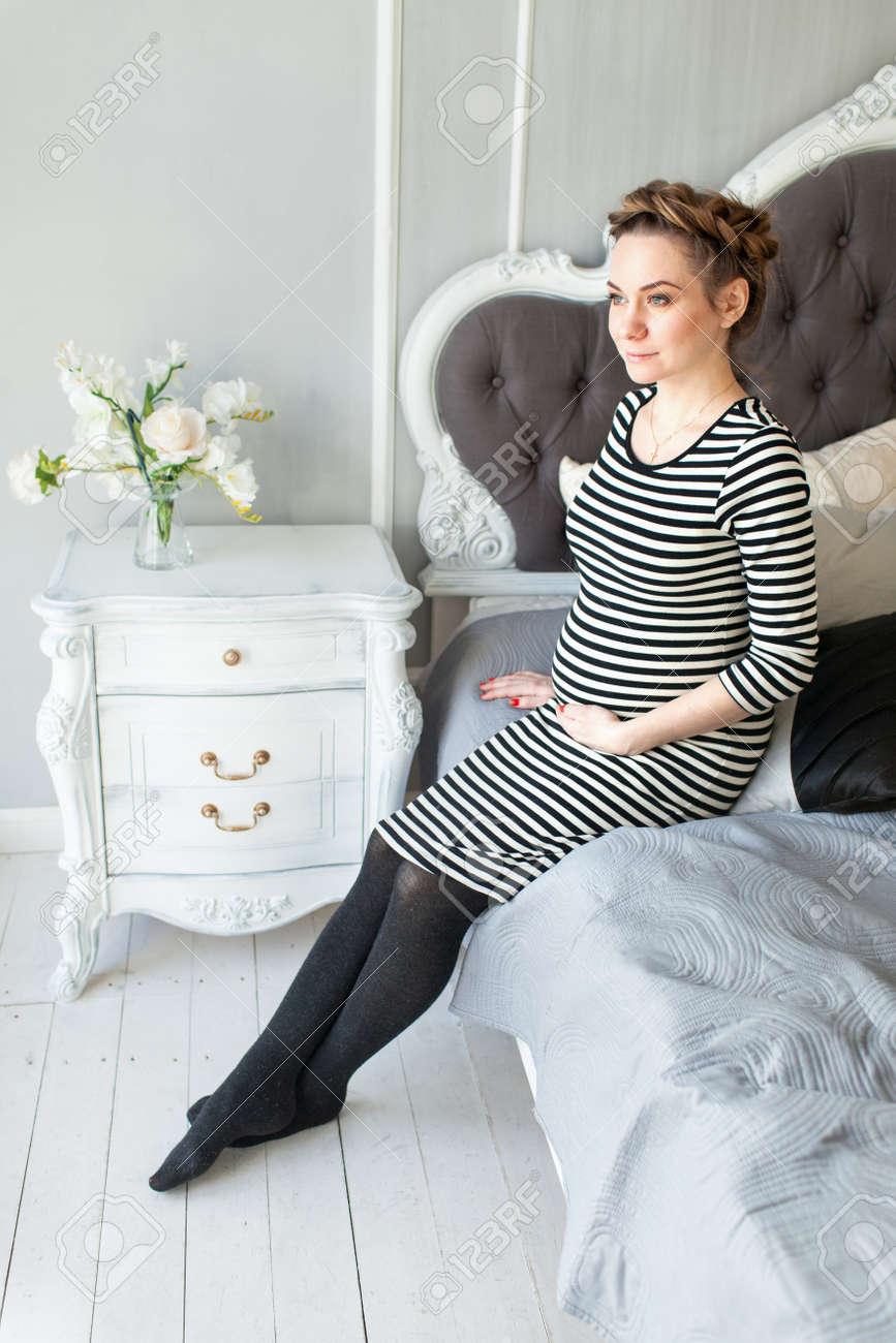 19a4da5cd Foto de archivo - Mujer embarazada hermosa joven en un vestido de rayas  francés sentado en la cama sonriendo.