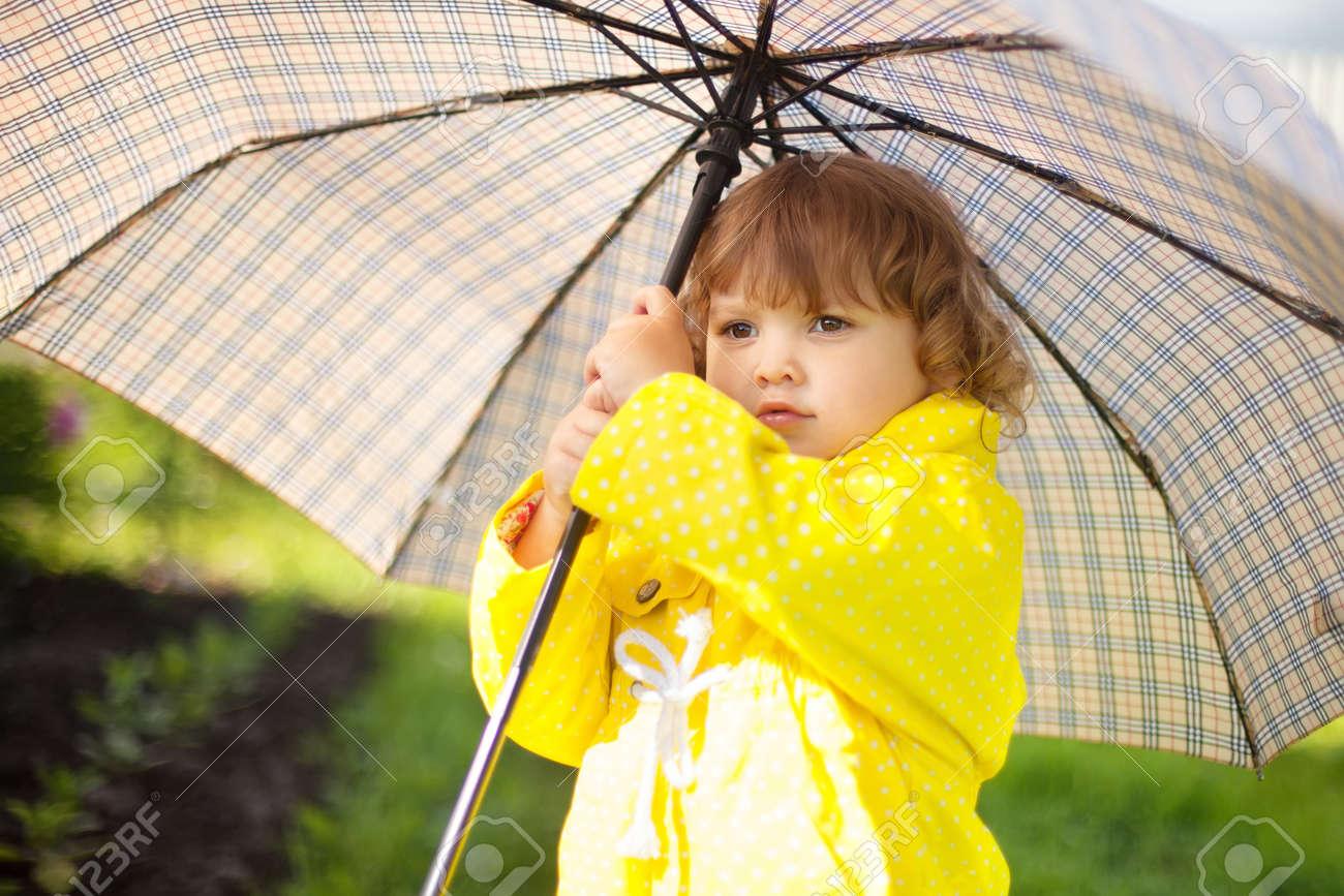 Adorable Fille Frisée Bambin Porte Manteau Imperméable Jaune Tenant Grand Parapluie Adulte Sous La Pluie En Jour Dautomne