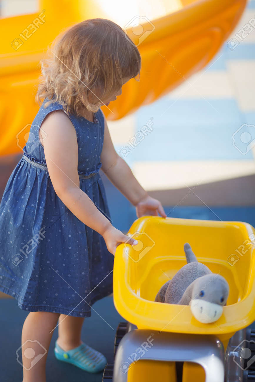 Cute Happy Toddler Girl Playing With Boys Toys On A Playground