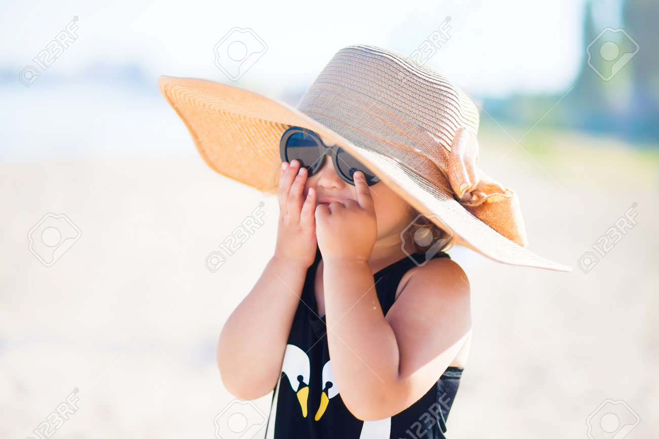 Elegant Toddler Girl Wearing Straw Hat And Sunglasses At The.. Stock ... dae47fbd337