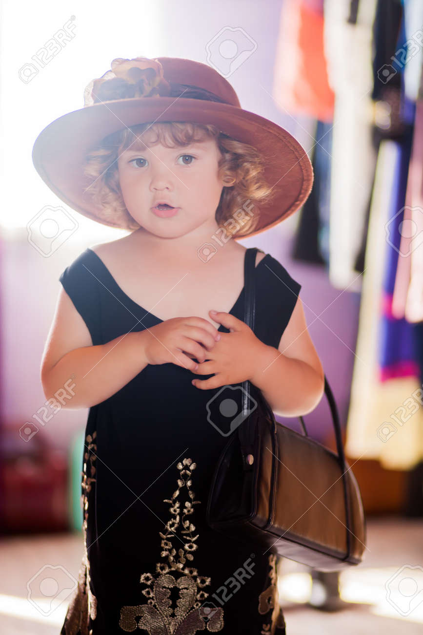 Little girl wearing mothers clothing evening dress and felt hat,