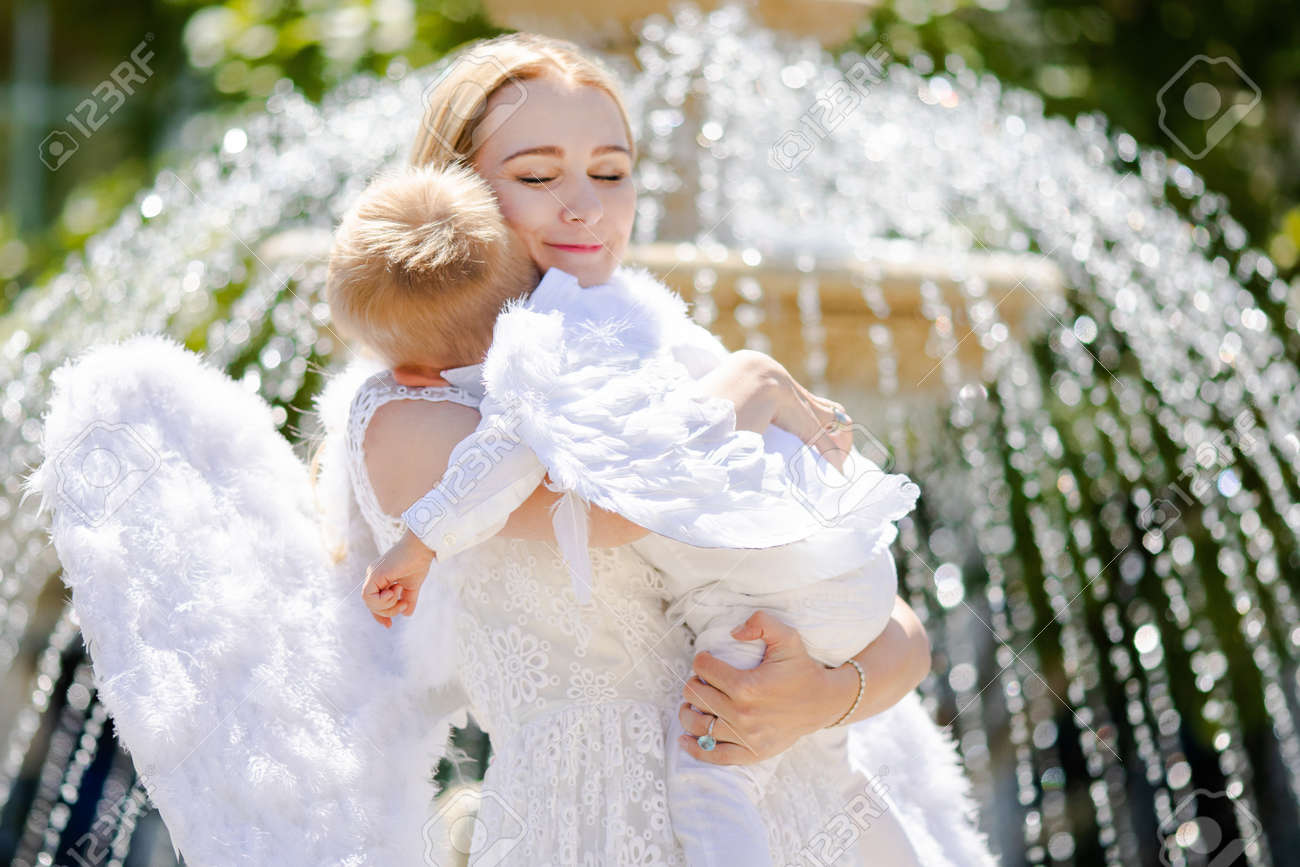 bbf8ea910 Beautiful mother and her toddler son wearing angel costumes. Cheerful  moment, loving family.