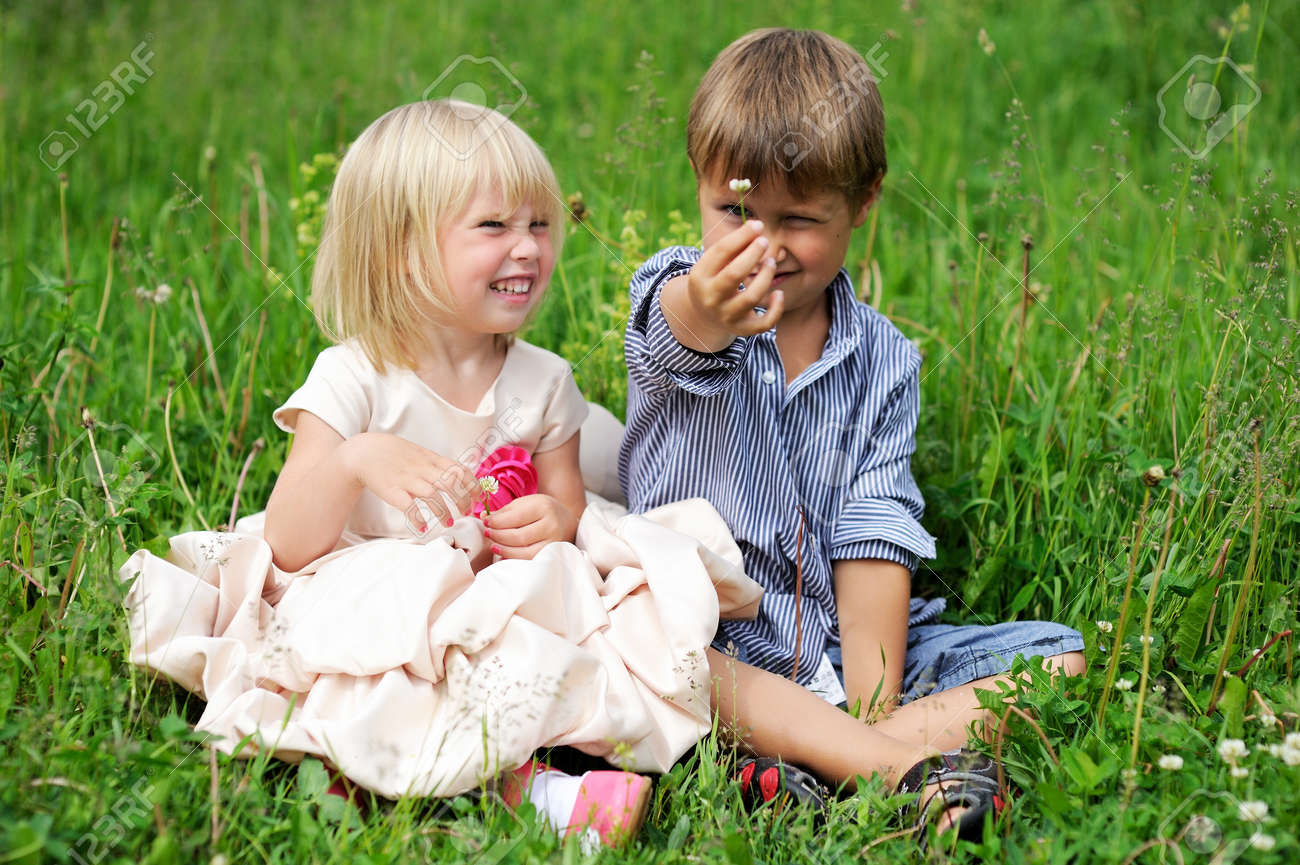 portrait of cute child boy and girl sitting on green grass stock