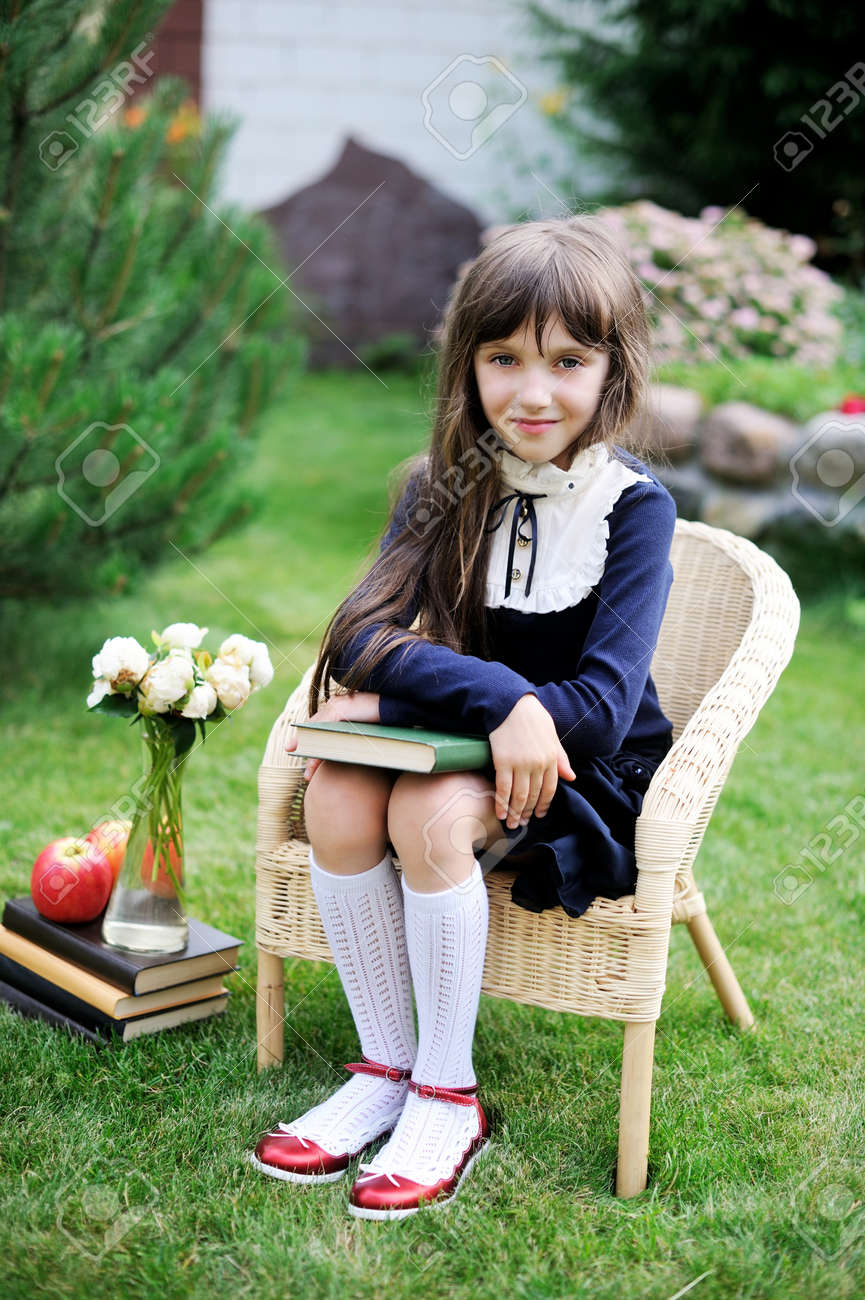 Cute young girl in navy school uniform sitting with a book in the garden Stock Photo - 22339071