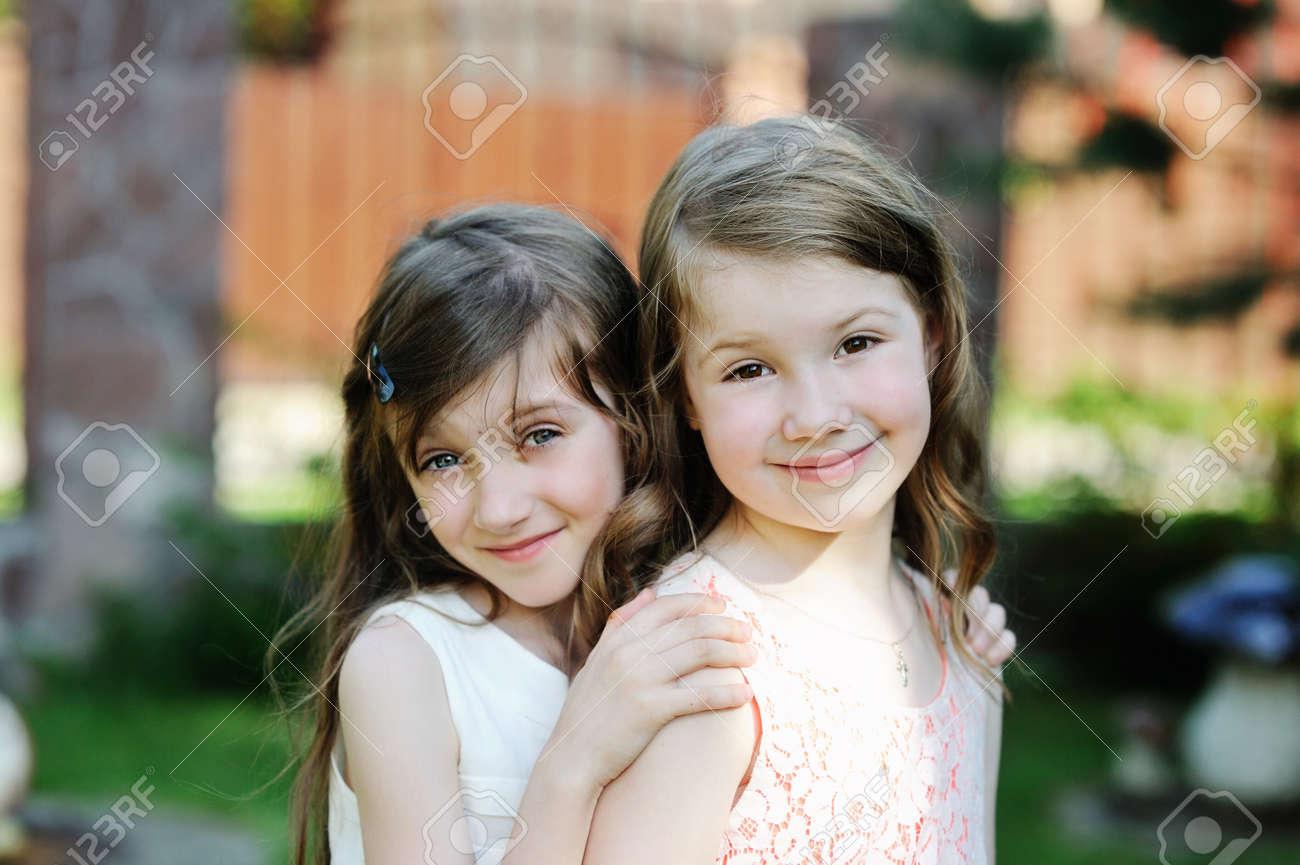 zwei junge mädchen in elegante kleider zusammen im garten