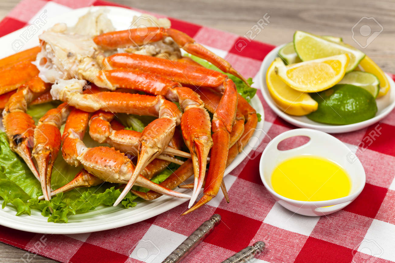 snow crab legs with fresh lemon slices and butter sauce stock