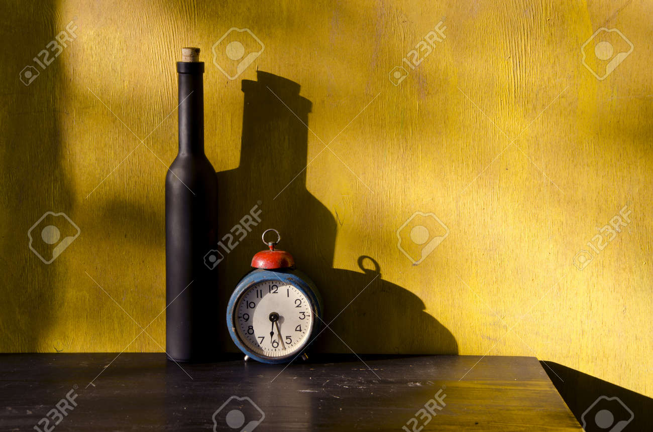 stiil-life with black bottle and old clock on yellow background - 11327047
