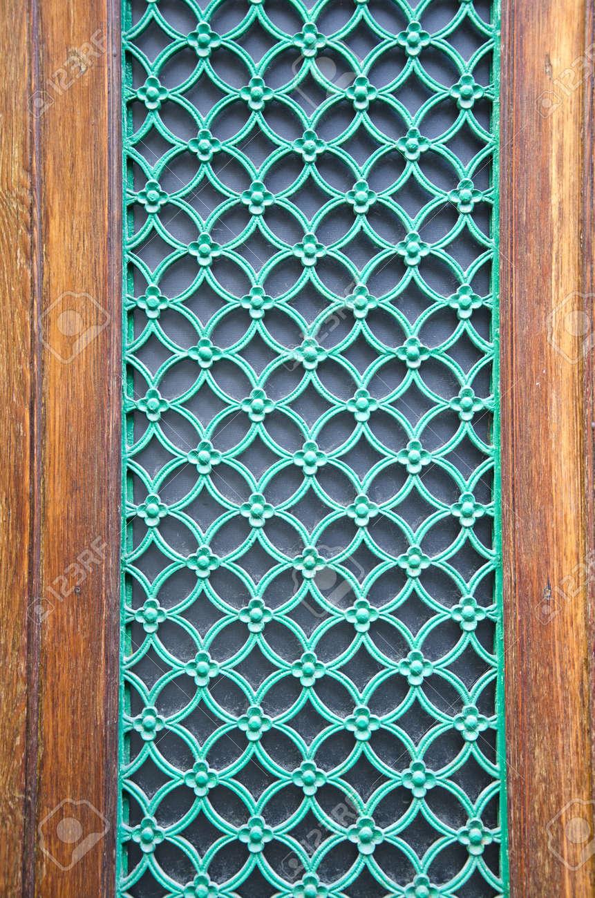 Green Painted Decorative Metal Grate On City Door Stock Photo