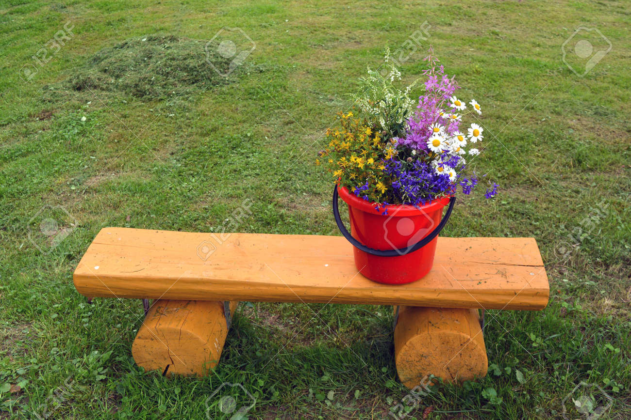 Various summertime wild flowers bouquet on yellow wooden bench in garden Stock Photo - 73478625