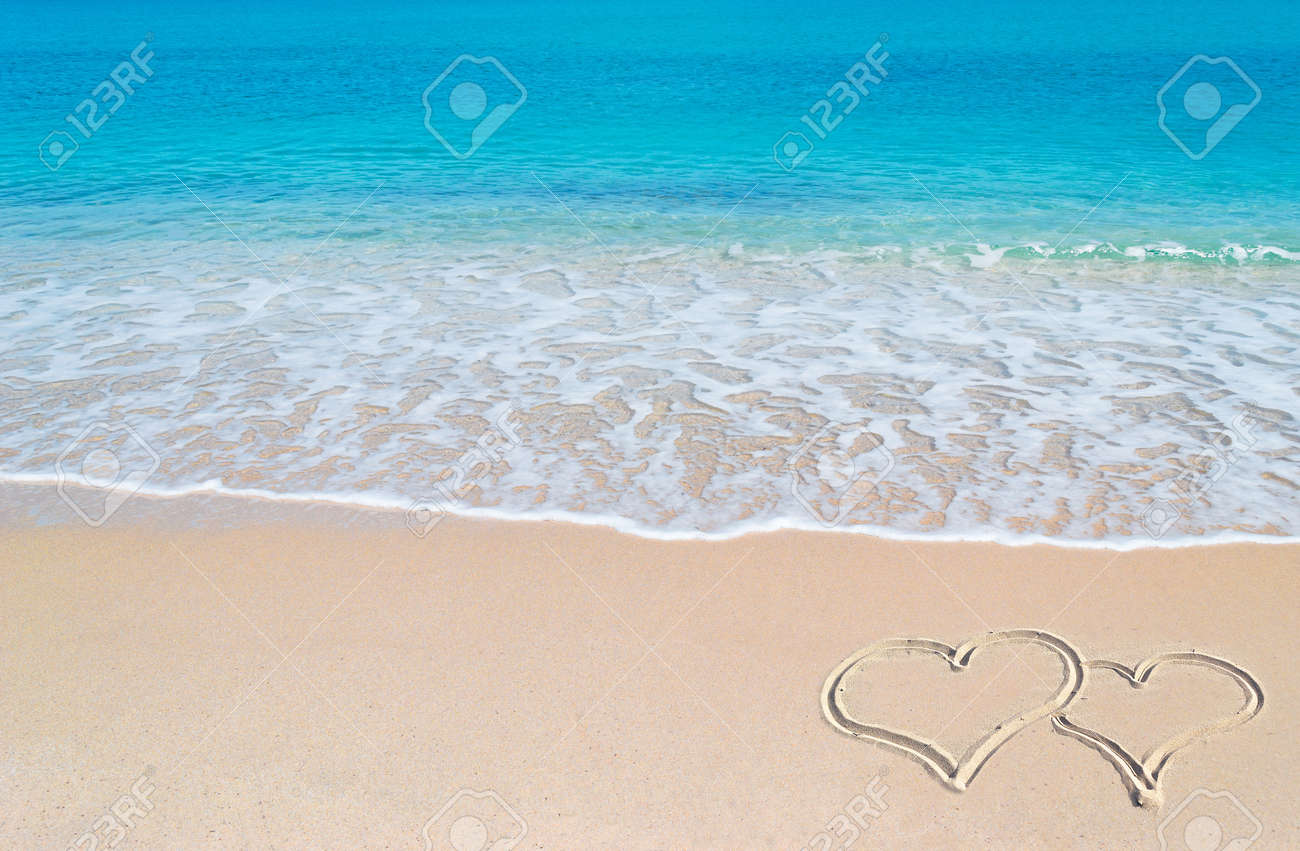 turquoise water and golden sand in Sardinia with two hearts drawn in the sand - 18917023