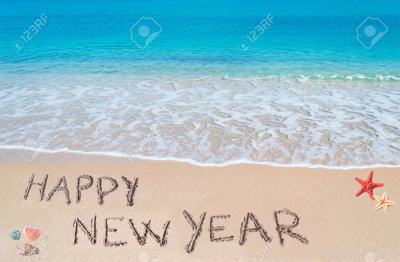 stock photo happy new year written on a tropical beach