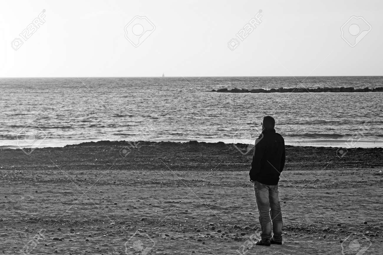 Man alone at the beach in winter black and white shot