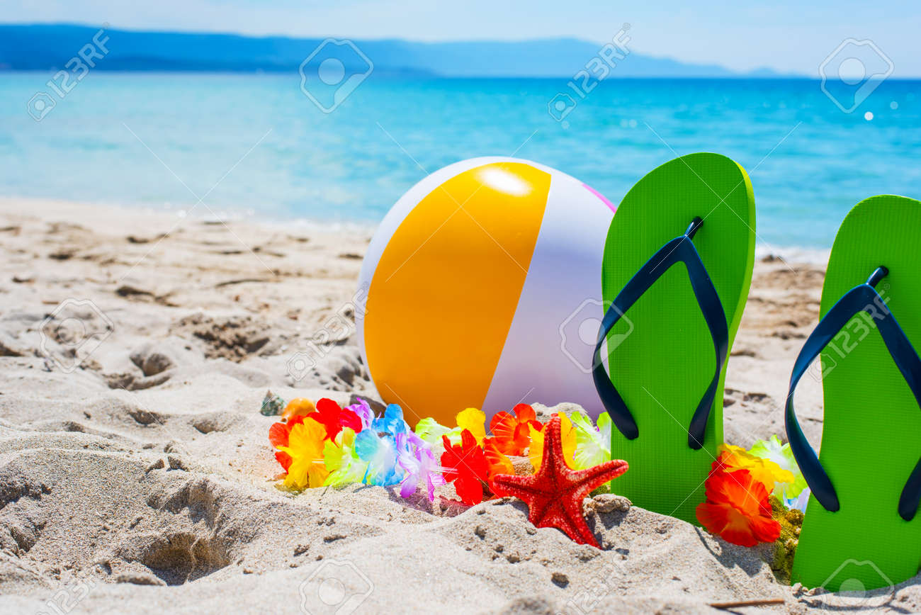 Beach ball in sand Floating Green Flip Flops And Beach Ball On The Sand Stock Photo 62191333 Visit Coastal Alabama Green Flip Flops And Beach Ball On The Sand Stock Photo Picture And
