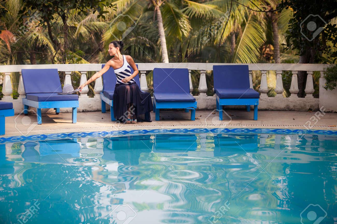 Fille brune en noir et blanc rayé piscine costume assis et en posant dans  l\'eau bleue dans la piscine avec des palmiers sur fond vert