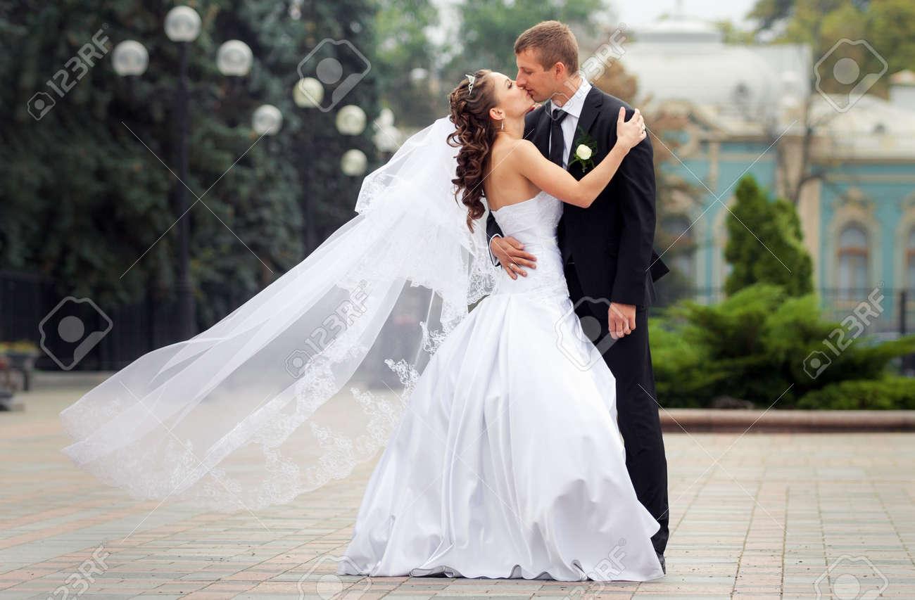 Foto de archivo , novia hermosa morena en vestido de novia blanco besar su  joven novio guapo en negro soporte traje en fondo grande de la ciudad