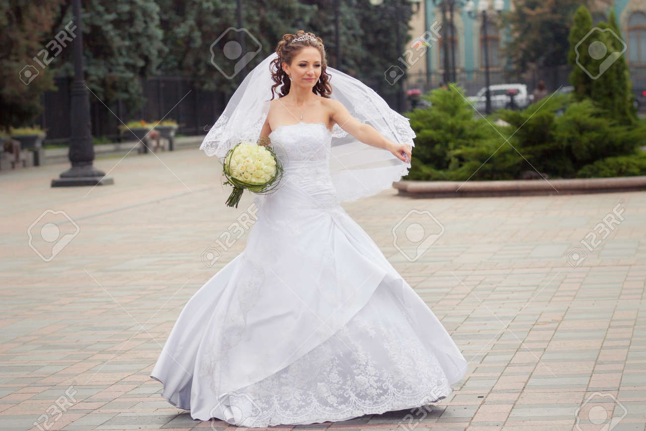 Beautiful Brunette Bride In White Wedding Dress Hold Her Bridal ...