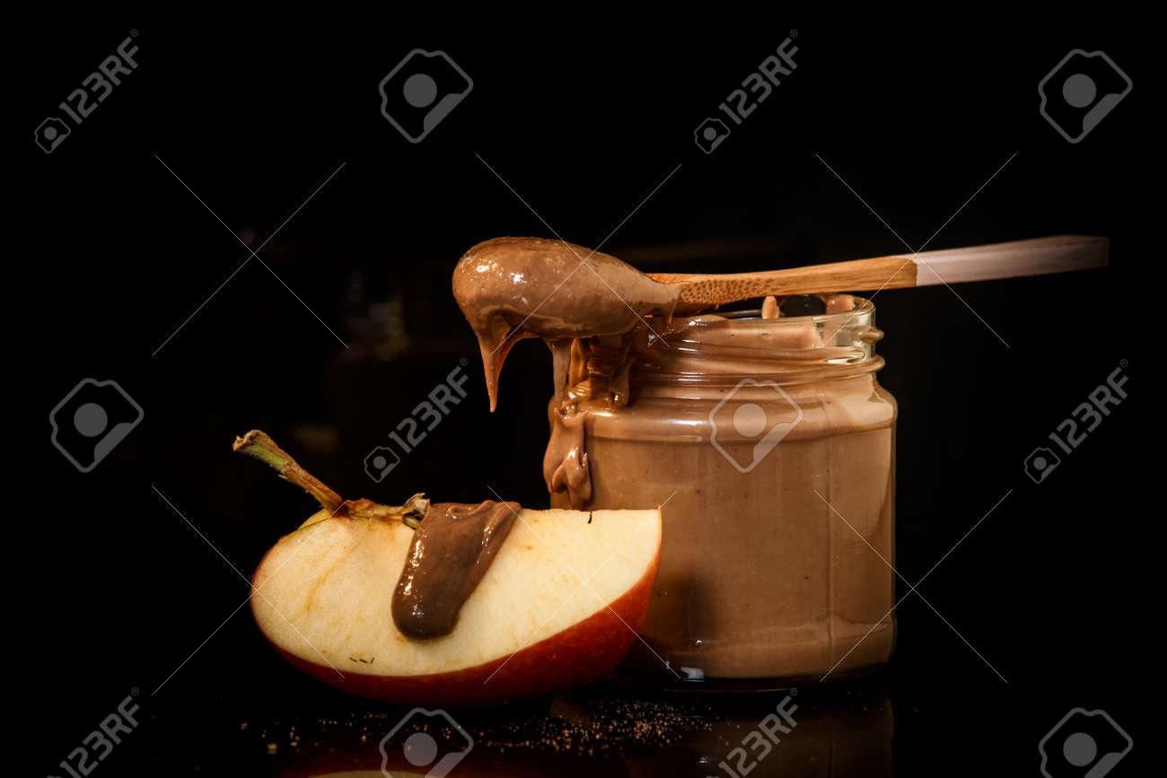 Closeup Chocolate Peanut Butter In Small Glass Jar With Wooden