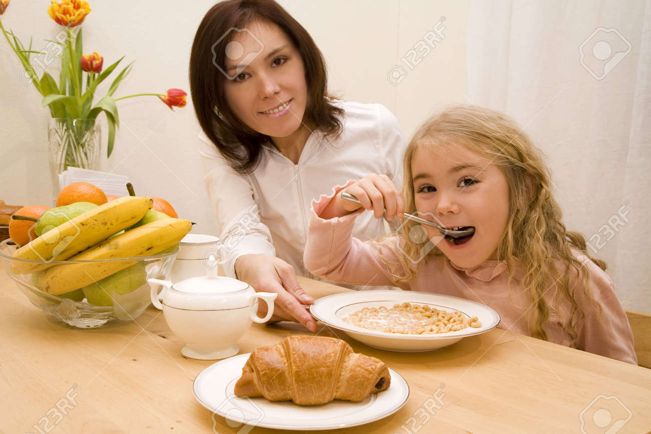 Young woman and her daughter having breakfast Stock Photo - 2576106