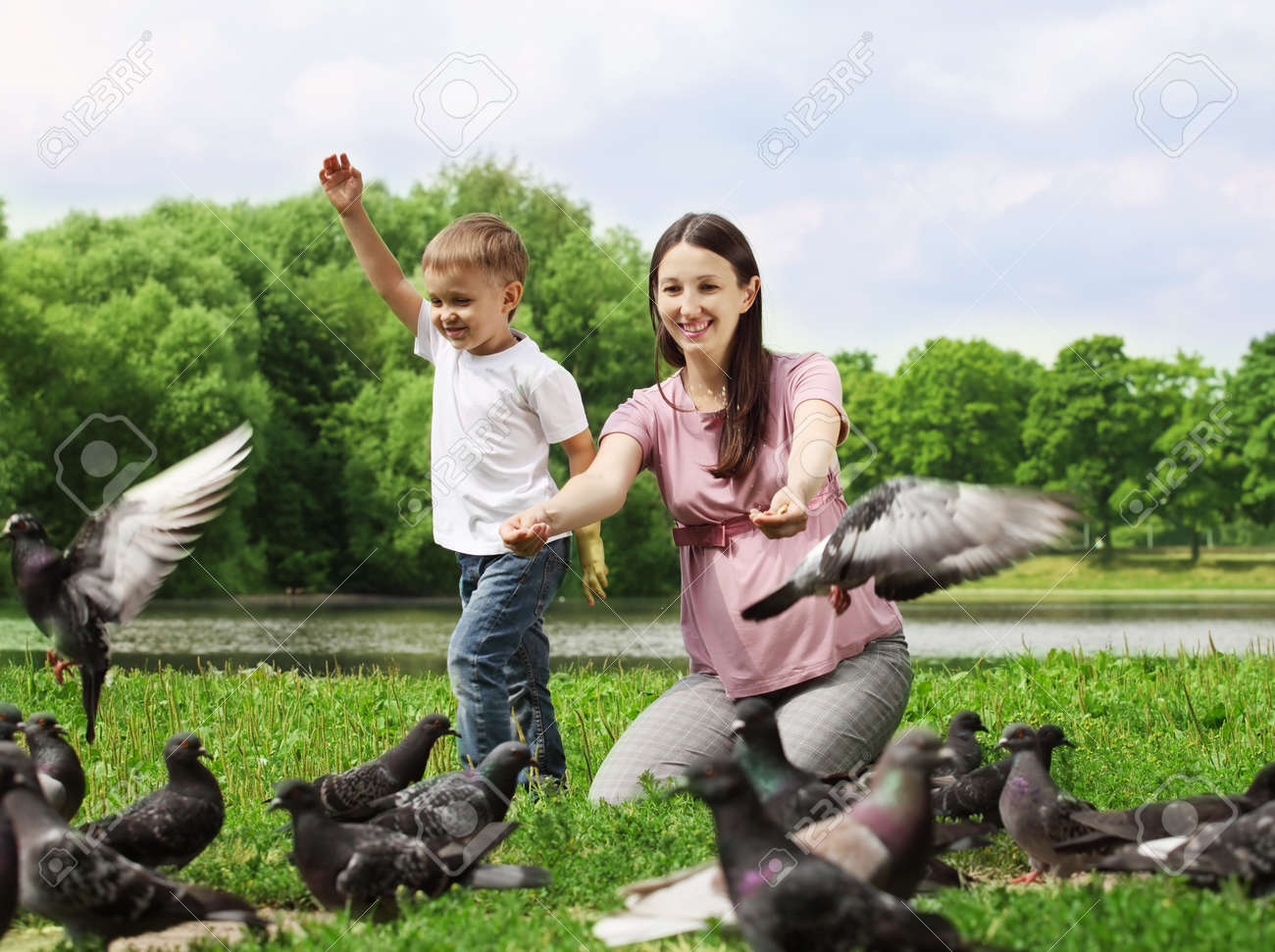 Pregnant woman with her son feeding pigeons in a park Stock Photo - 10417684
